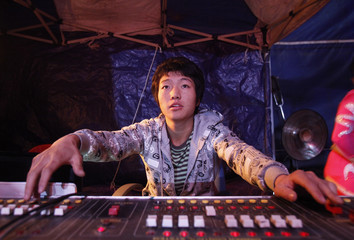 Shin, one of acrobats at the Dong Choon Circus Troupe, adjusts lighting equipment during a performance at its tent theatre in Seoul