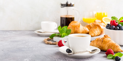 Healthy breakfast with coffee, croissants, fresh berries and orange juice on light gray background, selective focus, copy space.