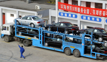 WORKER DIRECTS A TRAILER CARRYING CARS FOR DELIVERY IN SHANGHAI.