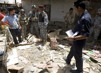 Policemen inspect the site of a roadside bomb attack in Baghdad