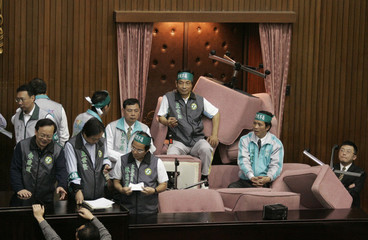 Legislators from the ruling Democratic Progressive Party block the door with chairs to delay the entrance of Parliament speaker Wang in Taipei