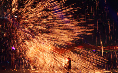 A dancer is silhouetted by fireworks during the opening ceremony of the 4th East Asian Games in Macau