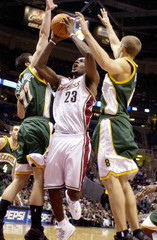 James of Cleveland Cavaliers is double-teamed by Radmanovic and Ridnour of Seattle SuperSonics in Cleveland
