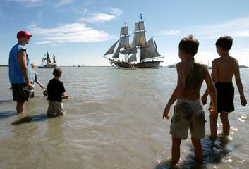 Children watch the Brigantine Lady Washington pass during a parade of tall ships in Richmond, Britis..