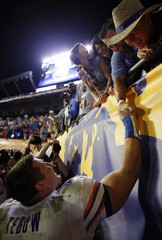 Florida Gators Tim Tebow shakes hands with fans as he leaves the field after defeating the Oklahoma Sooners in the NCAA's BCS National Championship football game in Miami