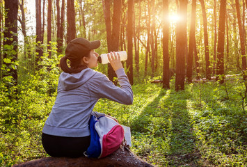 Girl hiker with backpack drinks water in the forest