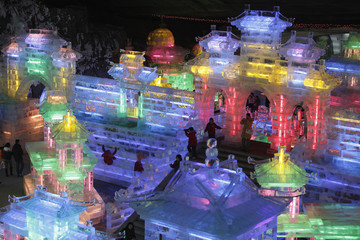 Visitors walk on ice sculptures in the shape of traditional Chinese buildings at the Ice Lantern Art Festival held on the outskirts of Beijing