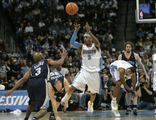 Denver Nuggets guard Allen Iverson passes over Memphis Grizzlies guard Chucky Atkins in the second quarter of their NBA game in Denver