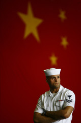 Navy Petty Officer Second Class Carlos Gomez stands in front of a big Chinese flag on the USS Kitty Hawk aircraft carrier while it is anchored in Hong Kong
