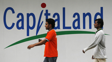 Men walk past a sign at a construction site just off on Singapore's main shopping boulevard Orchard Road