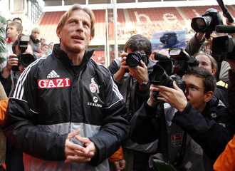 Daum, new head coach of German second division soccer club FC Cologne is surrounded by media during a training session with his new team in Cologne