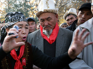 A woman gestures during an anti-presidential protest in front of state television in Bishkek