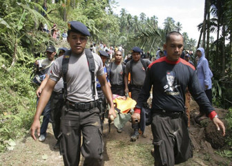 Rescue officials carry a body from a landslide in Padang Pariaman