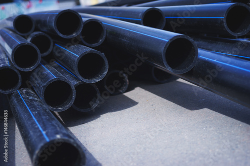 Stack of black plastic pipes for water supply or sewerage