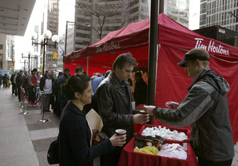 People line up for free Tim Hortons coffee and doughnuts outside Toronto Stock Exchange in Toronto