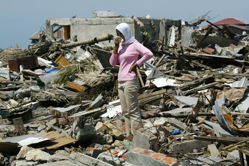 An Achenese woman stands alone amid debris in the tsunami-devastated city of Banda Aceh.