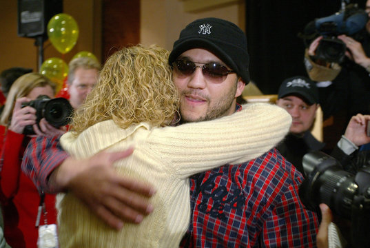 Powerball co-winner Maboussou hugs gas station employee Fisher after being awarded his share of jackpot in Nebraska