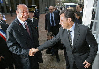 French President Chirac shakes hands with Interior Minister Sarkozy at the Seine-Saint-Denis prefecture in Bobigny