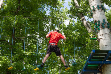 man in adventure park on  tree top