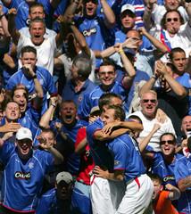 Rangers' Buffel celebrates scoring with Lovenkrands during Scottish Premier division soccer match ...