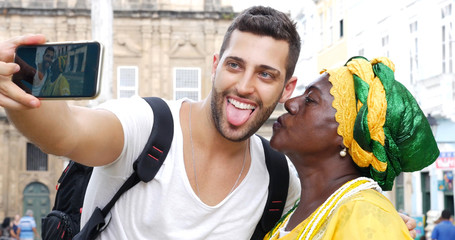 Tourist taking a selfie with a Baiana in the old colonial district of Salvador, Brazil