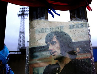 Rain drops are seen on a portrait of the Northern Ireland and Manchester United soccer legend George..
