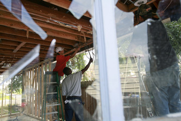 Workers remove damaged wood from a house in New Orleans