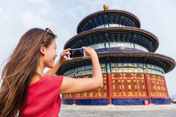 Asia travel chinese woman tourist taking picture with smartphone of the temple of Heaven, a popular tourist attraction which is an imperial building in Beijing city. Famous china landmark.