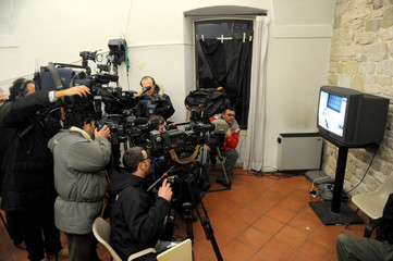 Cameramen and photographers take footage and pictures of a television showing Rudy Guede's closed appeal trial in the pressroom at the courthouse in Perugia