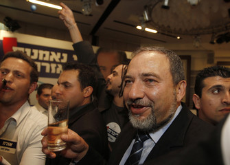 Avigdor Lieberman holds a glass of champagne as he celebrates with supporters in Jerusalem