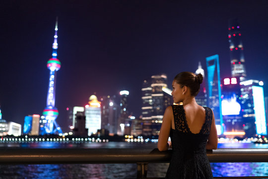 Elegant asian woman in evening dress relaxing by the Bund river in Shanghai looking at the night city lights of Pudong skyline. Luxury travel lifestyle.