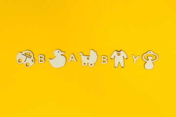 "The word ""baby"" on a yellow background was mixed with wooden figures of toys."