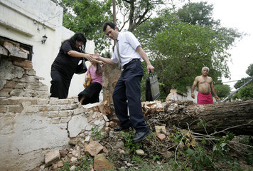 Pedestrians climb over a wall destroyed by an uprooted tree after a thunderstorm in Asuncion
