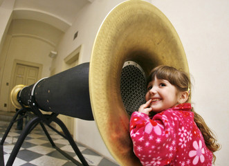 A girl listens to a device at an interactive exhibition