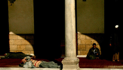 Egyptians rest as foreign student reads Koran inside al-Azhar Mosque in Cairo
