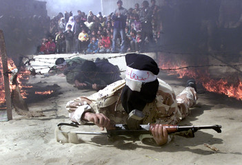 MASKED PALESTINIAN GUNMEN CRAWL BENEATH WIRE DURING A RALLY IN RAFAH.