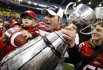 Stampeders Chevrier and son Luke celebrate with Grey Cup after defeating Alouettes during CFL's 96th Grey Cup football game in Montreal