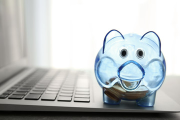 Transparent piggy bank and laptop on blurred background, closeup