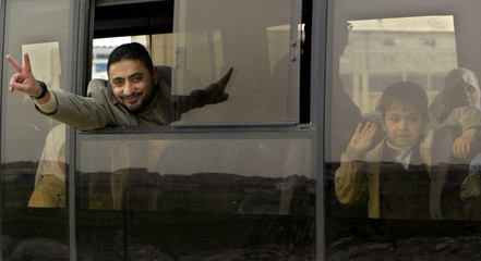 A Palestinian deportee making a victory sign while he is inside a bus at Erez check point, North of ...