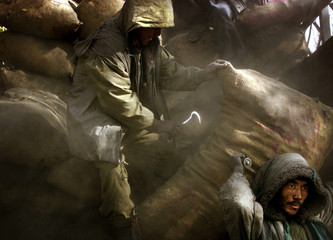An Afghan man carries a bag with coal to be ditributed to poor people in Kabul November 28, 2001. [R..
