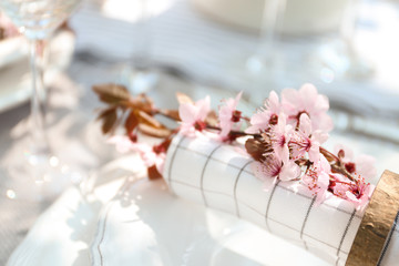Napkin with branch of flowers on plate, closeup