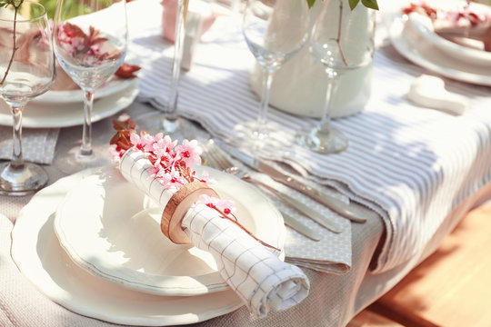 Plate with napkin and branch of flowers on served festive table
