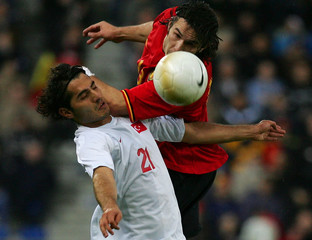 Belgium's Hoefkens jumps for the ball with Turkey's Altintop during their friendly soccer match in Genk