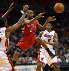 Toronto Raptors Will Solomon leaps to pass off against the defense of Miami Heat's Udonis Haslem and Yakhouba Diawara  during second quarter NBA action in Miami