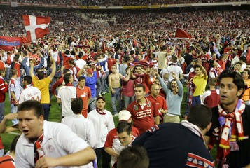 Sevilla's supporters crowd the field after their team won their UEFA Cup semi-final match against Schalke 04 in Seville