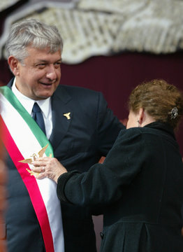 """Andres Manuel Lopez Obrador receives the presidential sash from lawmaker Rosario Ibarra during his swearing in ceremony as """"legitimate president"""" at Mexico City's Zocalo square"""