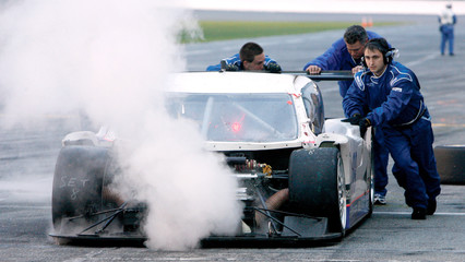 The crew members of the number 09 Spirit of Daytona Racing push the car behind the wall after the radiator blew at the Rolex 24 at Daytona