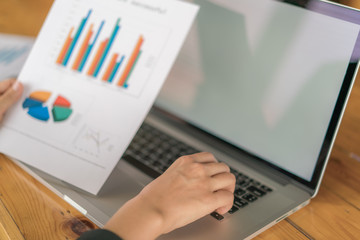 Business woman hand with Financial charts and laptop on the table .