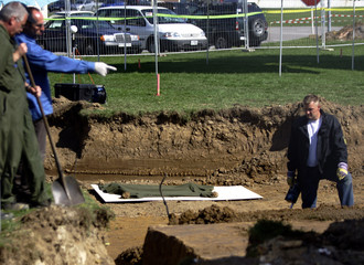 Police men examine grave at the US Army airfield in southern German city of Leinfelden-Echterdingen.