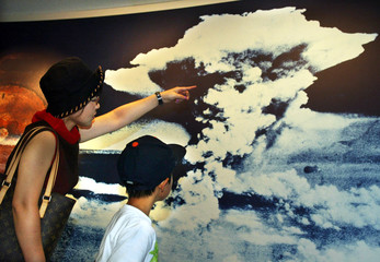 A mother and son look at a picture of the mushroom cloud atomic bomb blast as they visit Hiroshima P..